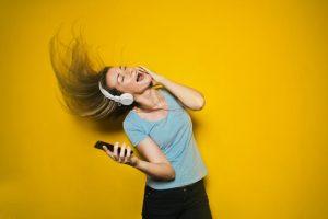 Devojka igra sa bežičnim slušalicama